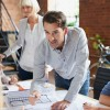 Architects working on plans at business boardroom table