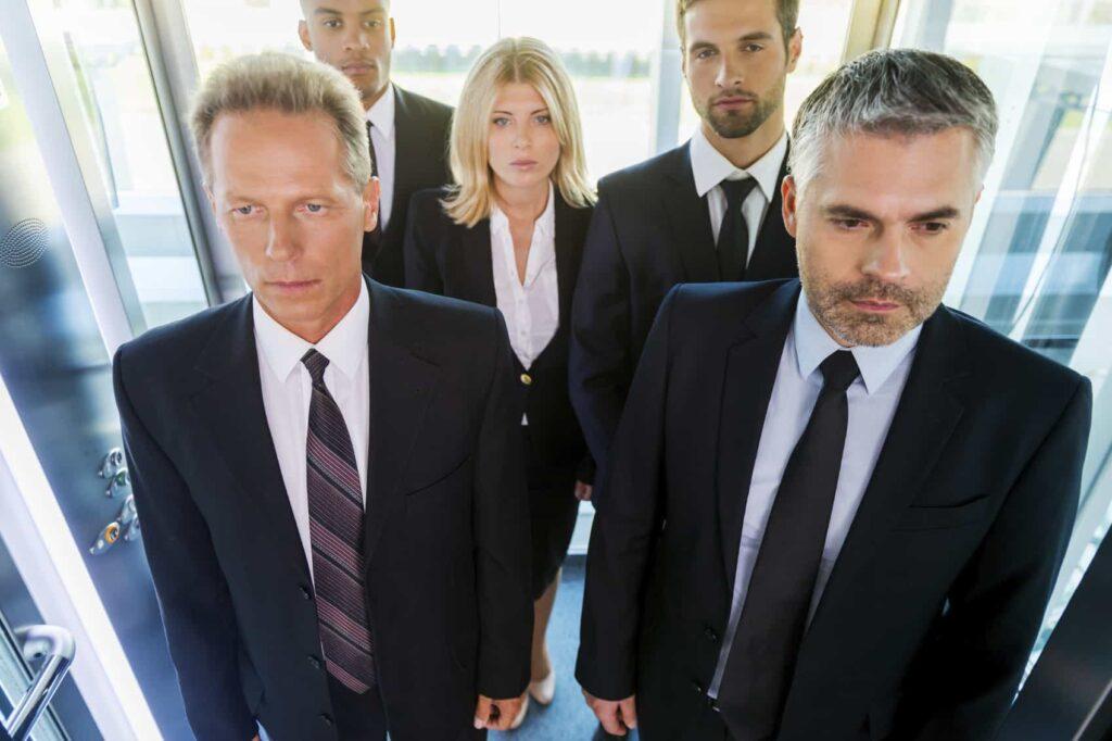 People in elevator. Top view of business people in formalwear standing in elevator