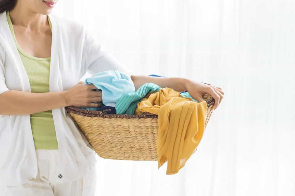 Cropped image of woman holding a laundry basket full of clothes
