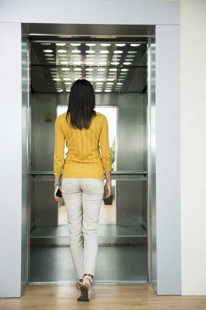 Back view portrait of a woman going in elevator  683x1024 - The Rising Trend of Home Lifts in Luxury Homes