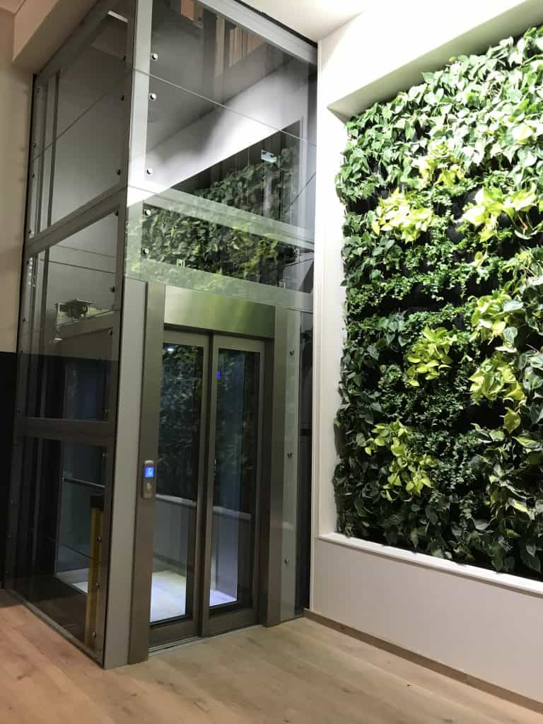 commercial lift with living wall next to it