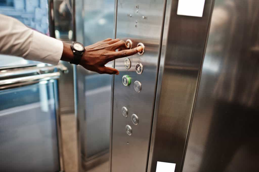 Close up photo of African american man hand with watches at elevator or modern lift, pushing button.
