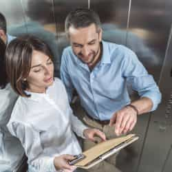 Talking in lift. Top view of pleasant couple is standing in elevator. Elegant woman is holding papers and smartphone while cheerful man is pointing at her documents with smile