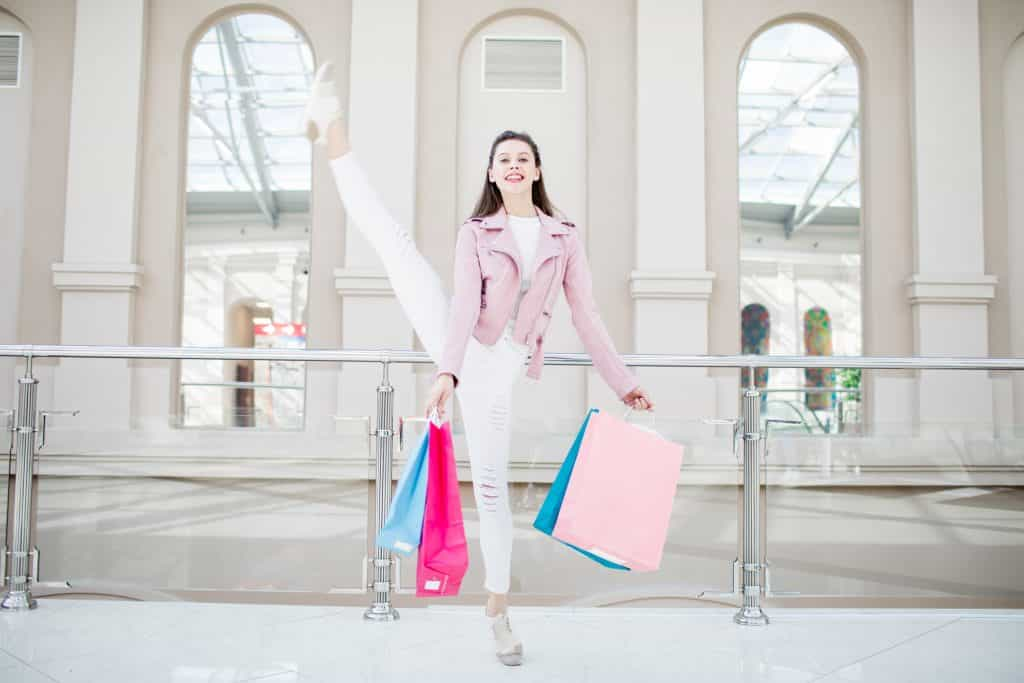 Positive excited flexible pretty girl in stylish jacket lifting leg demonstrating her stretching while enjoying shopping time in modern mall